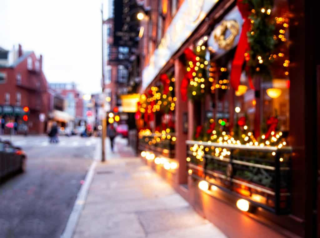 winter getaways in new england - lit up holiday city street in winter