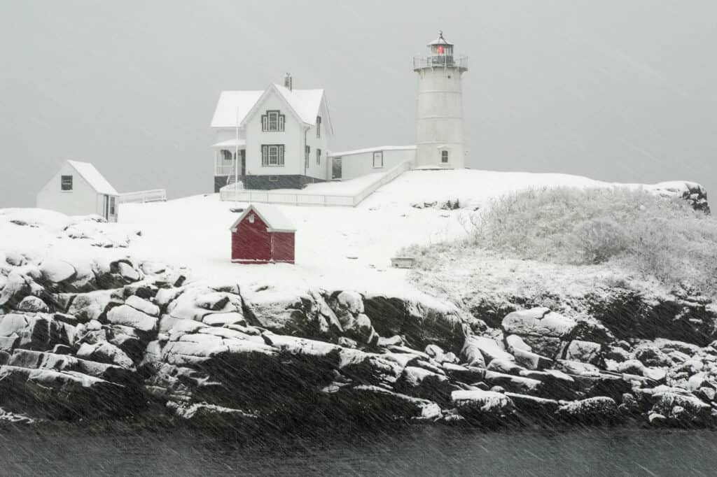 Nubble lighthouse, also known as Cape Neddick light, flashes its red light during a blizzard snowstorm in Maine, in New England.