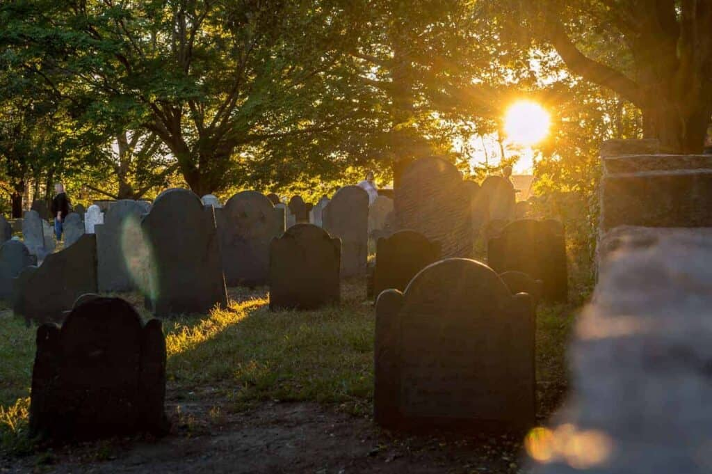 things to do in salem ma in october header - sun setting behind tombstones in graveyard