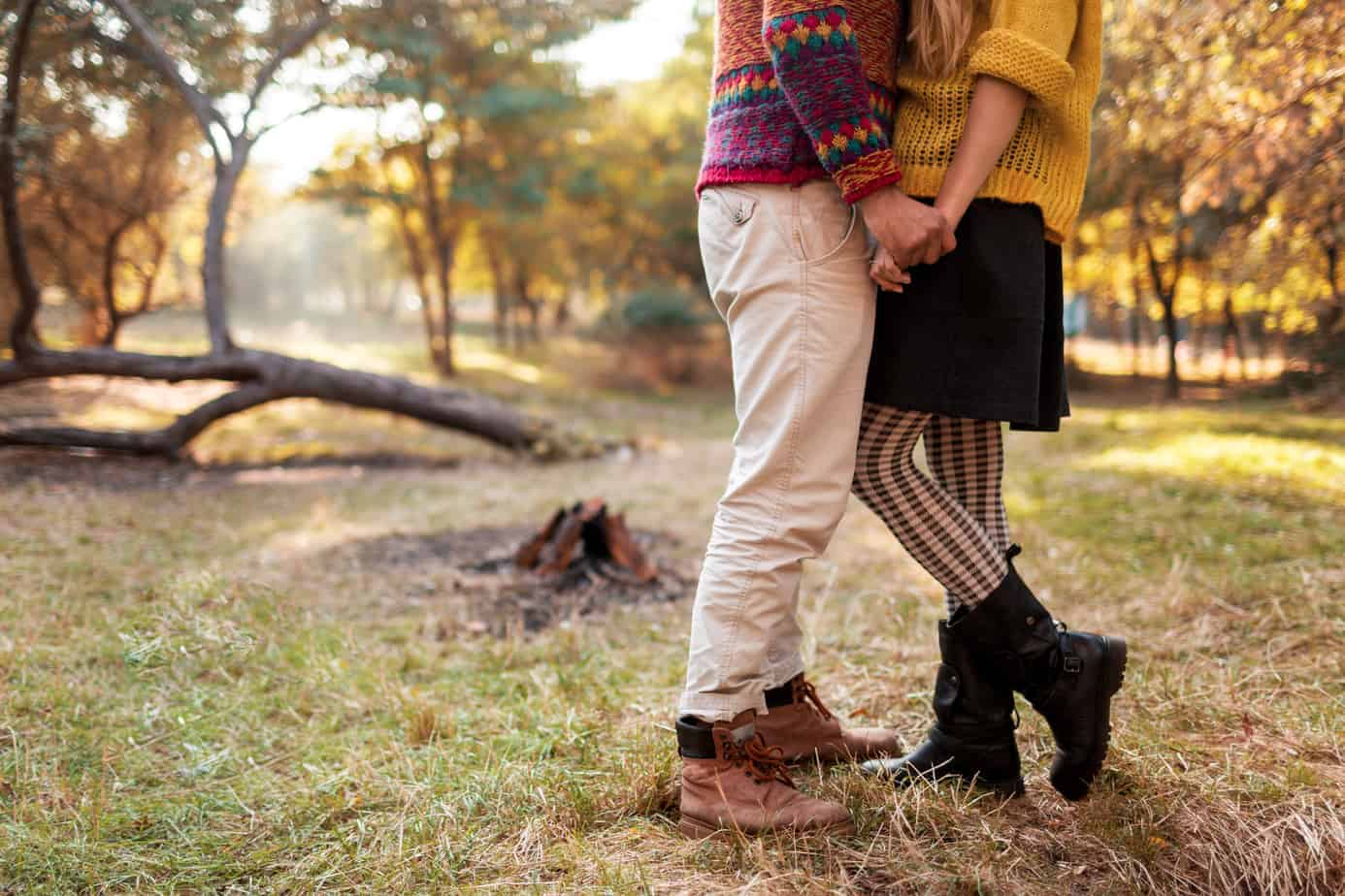 couple standing and holding hands in fall outdoor scene - enjoying romantic getaways in new england