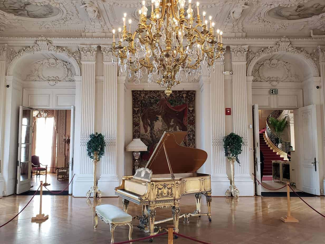 newport RI mansion tours header - luxurious gilden age mansion interior, ornate white walls in background, a gilded piano and impressive chandelier are in front