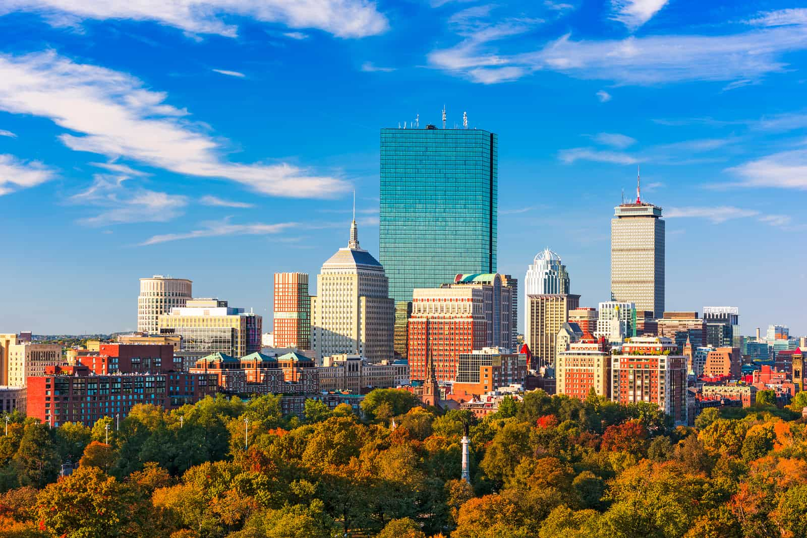 the Go Boston Card vs Boston CityPASS - image of boston skyline on a sunny day with blue sky and autumn trees