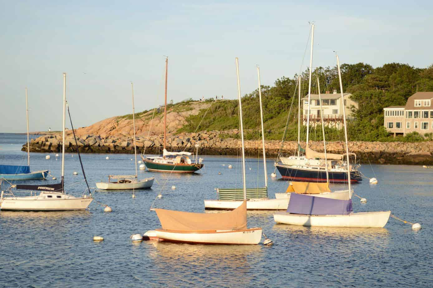 where to stay in rockport ma header image - colorful boats in rockport harbor, sunset golden hour