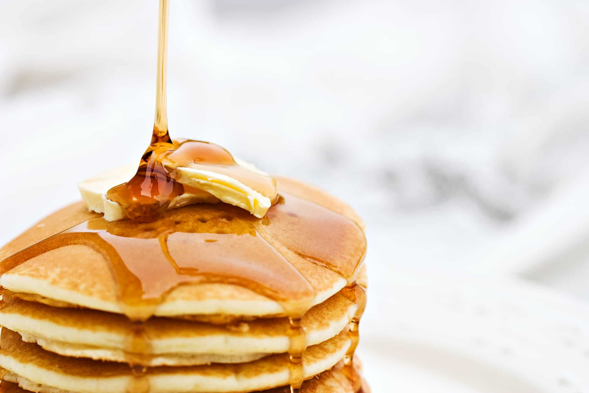 best breakfast in burlington VT header image - stack of golden pancakes with syrup dripping on them, white blurred background