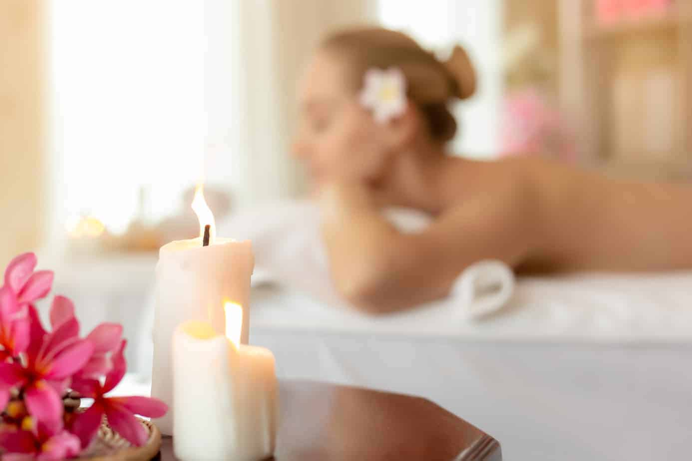 best spa getaways in new england header image - woman lying on massage table with lit candles in foreground