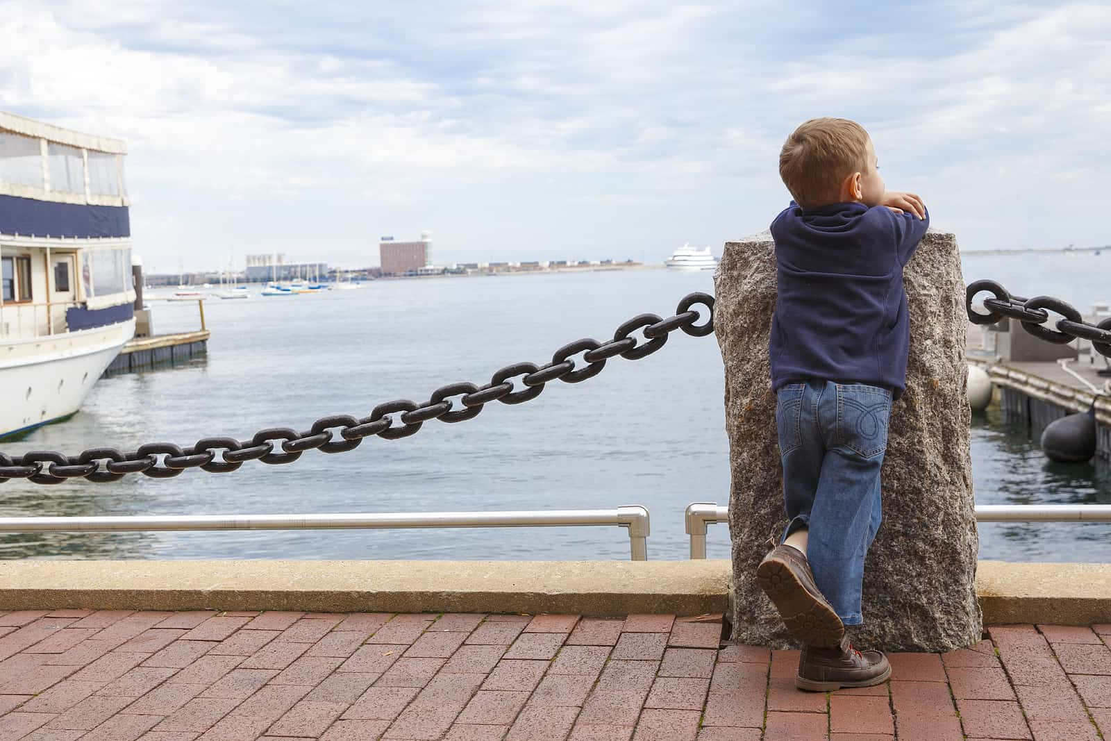things to do in boston with kids header image - boy in harbor. little kid looking at ships and sea.