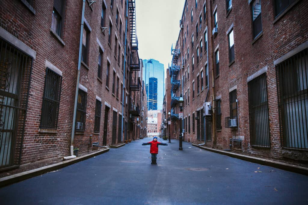 things to do with kids in boston - small child in red jacket standing in Boston alleyway between tall brick buildings