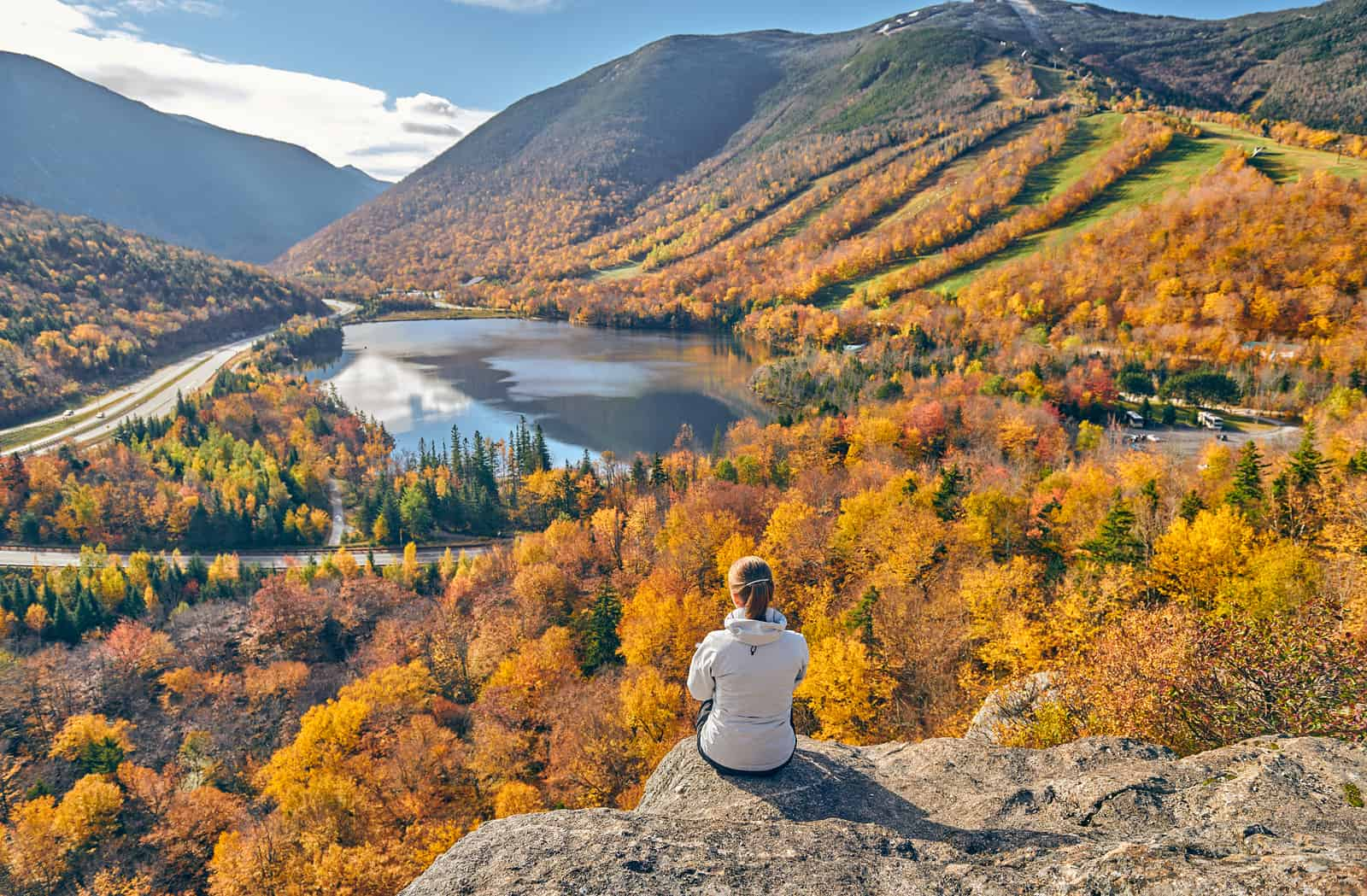 best hikes in new hampshire - Woman hiking at Artist's Bluff in autumn. View of Echo Lake. Fall colours in Franconia Notch State Park. White Mountain National Forest, New Hampshire, USA