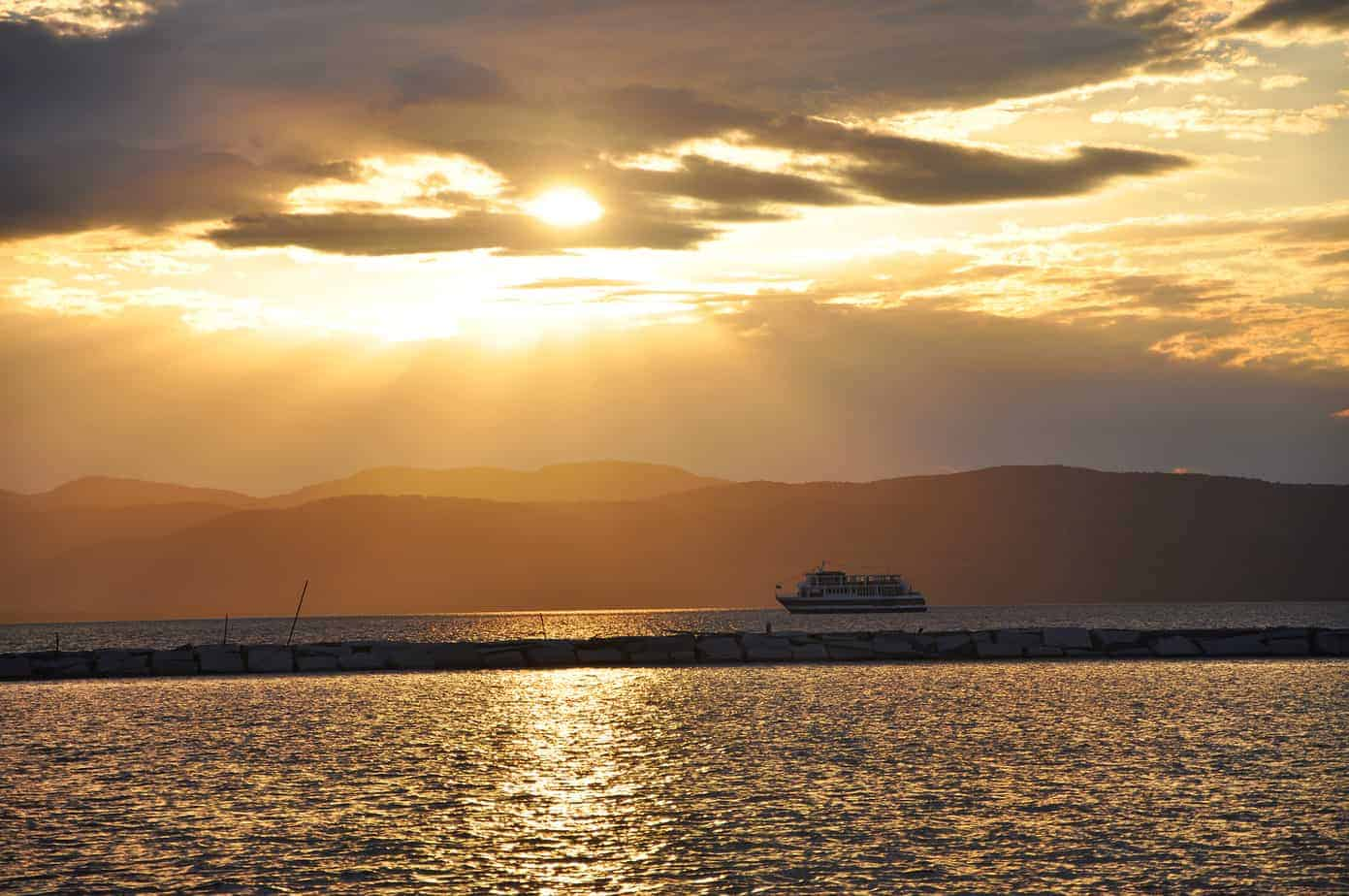 where to stay in burlington VT header - image of golden sunset over lake champlain with mountains in background