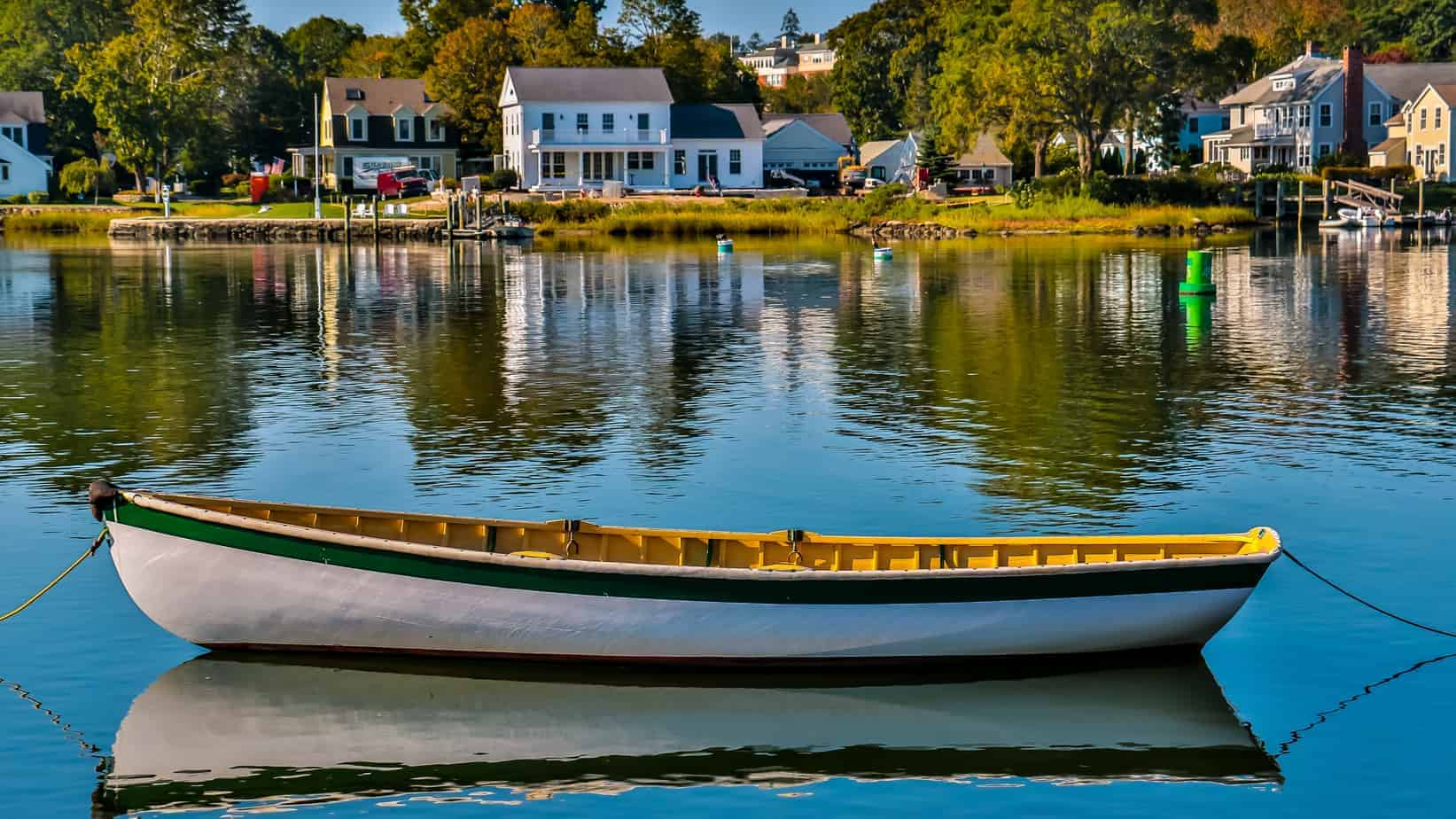 things to do in mystic CT photo of rowboat in foreground on still water, New England houses in background
