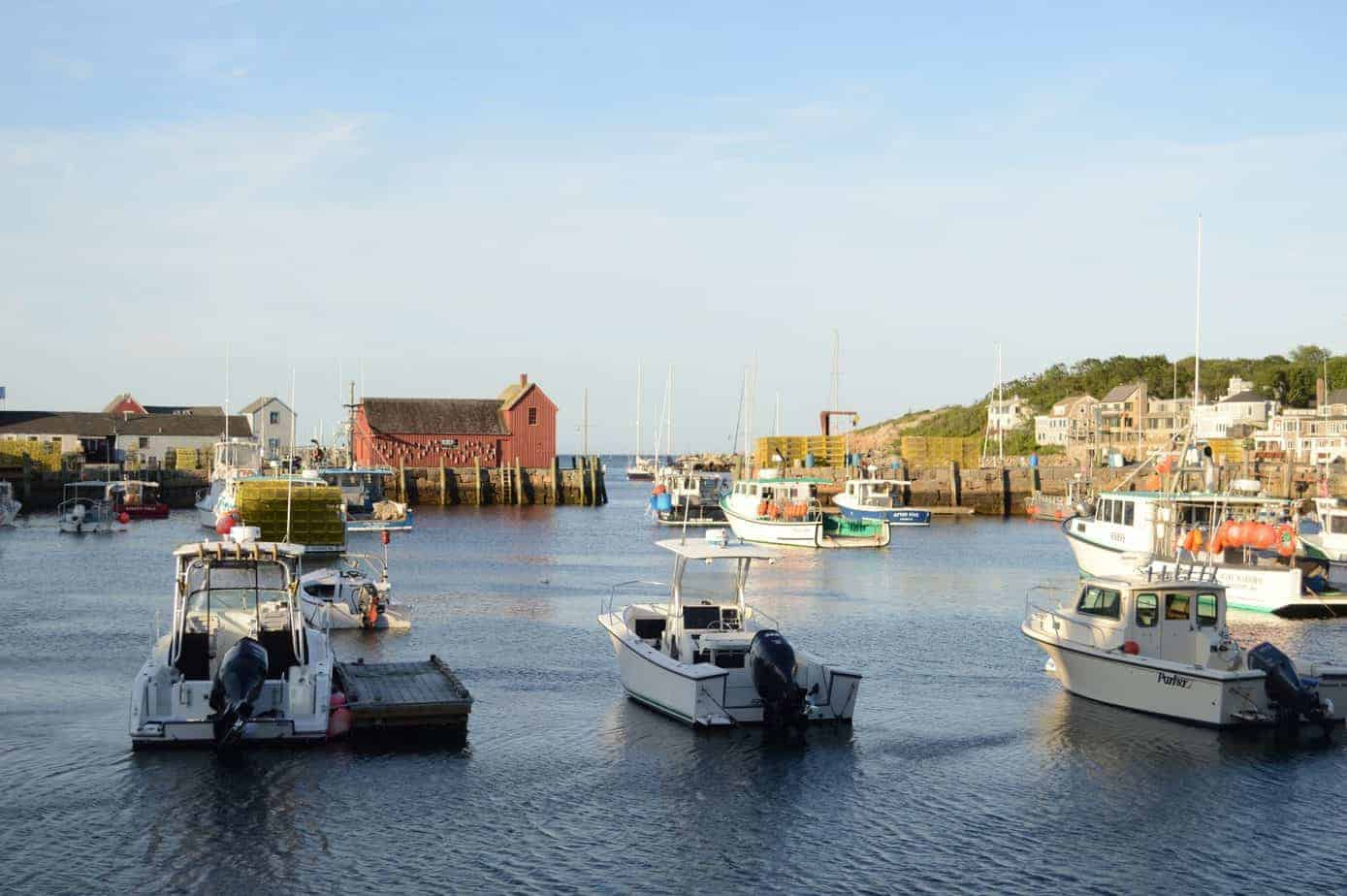 top things to do in rockport ma - image of harbor full of boats, water is calm, a red fish shack is prominent in the background
