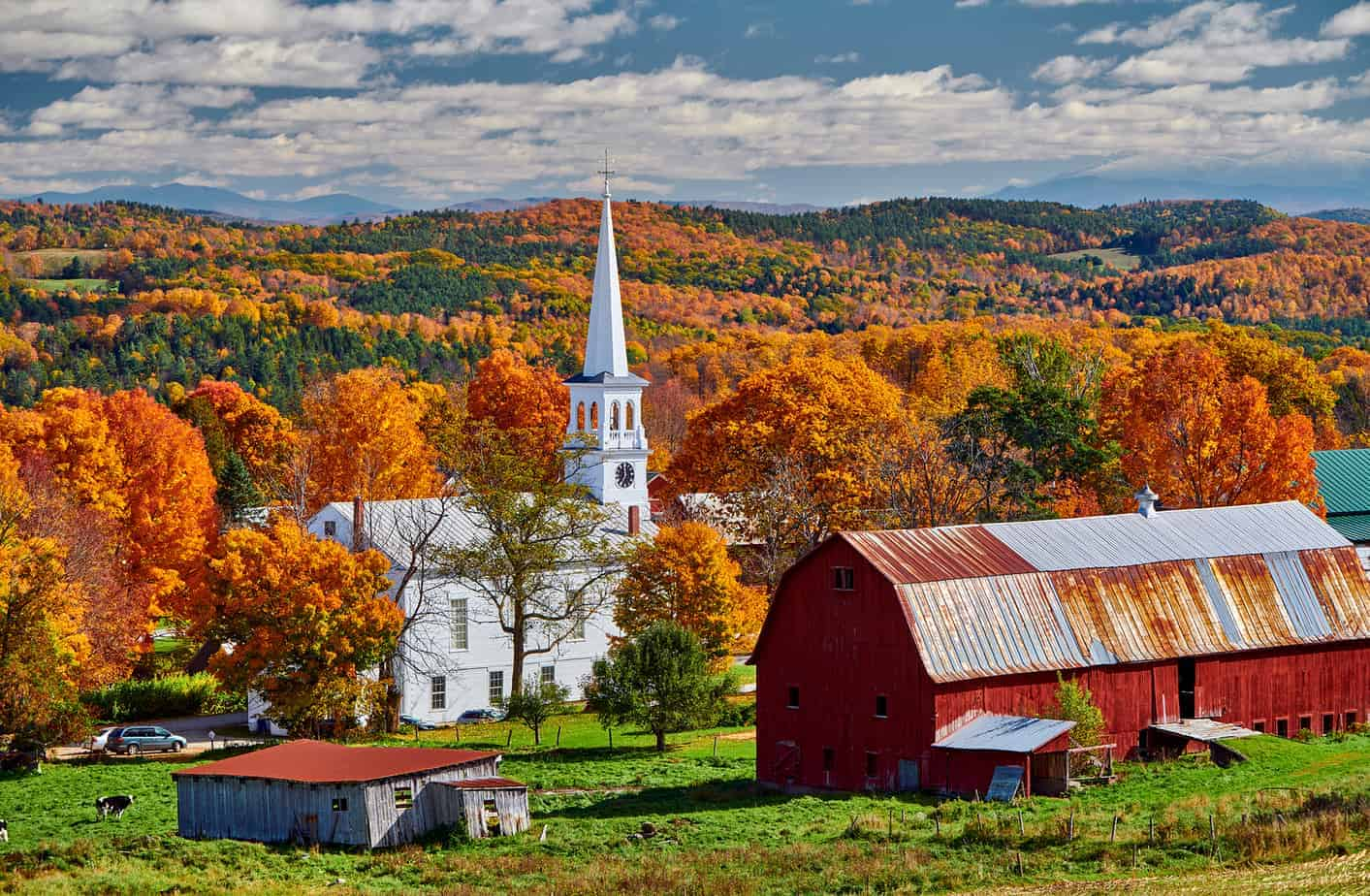vermont weekend getaway header image - photo of iconic vermont countryside in the fall with red barn and white church steeple