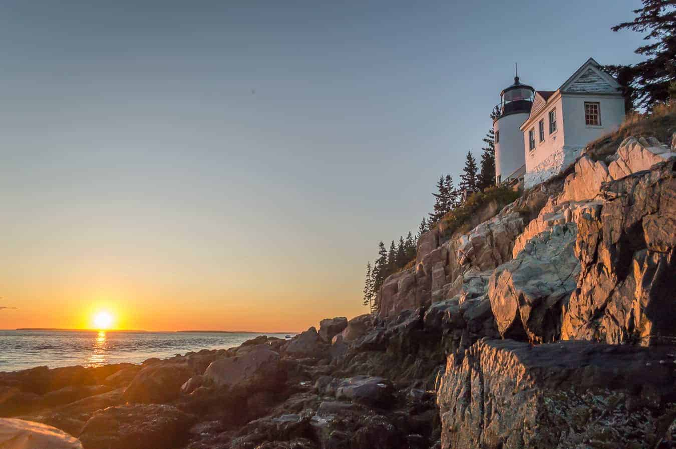 3 day itinerary acadia national park - image of small white lighthouse high on rocky hill, Maine coast, sunset over the ocean to the far left