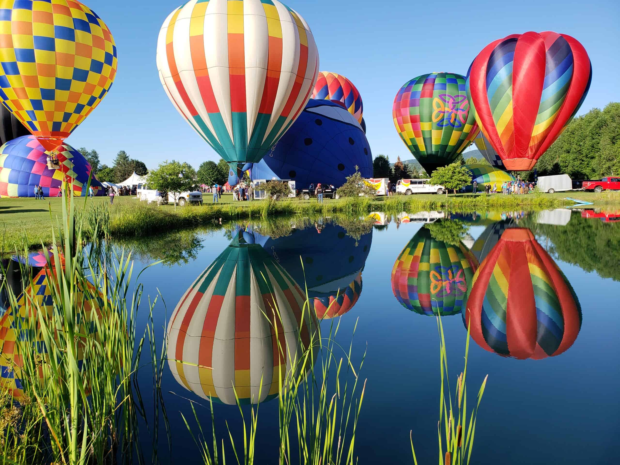 a group of colorful hot air balloons ready to take off, their colors are reflected in a still pond