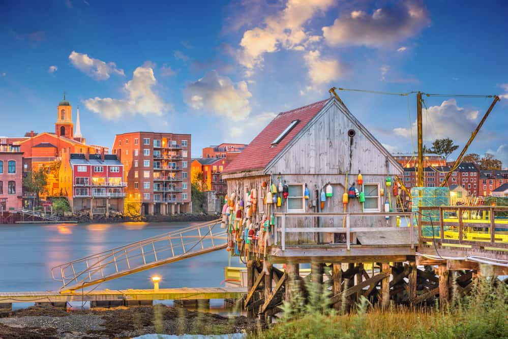 where's new england - image of portsmouth new hampshire waterfront. in the foreground is a fishing shack covered with colorful buoys, a traditional seaside town in the distance