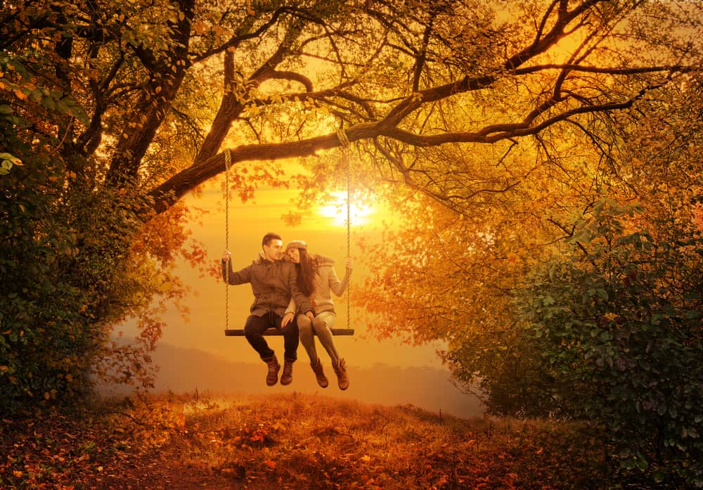 romantic getaways in vermont - image of couple swinging on a swing handing from a tree surrounded by orange fall colors