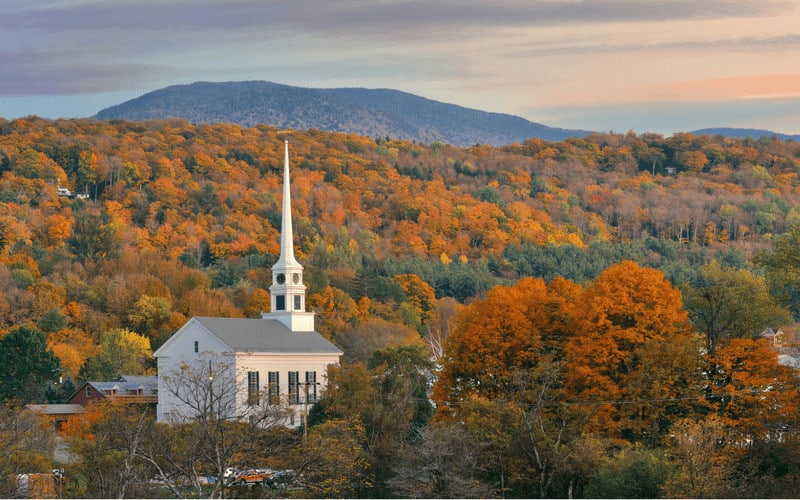 things to do in stowe VT - pastoral image of fall colors covering distant hills with a white steepled church in the foreground