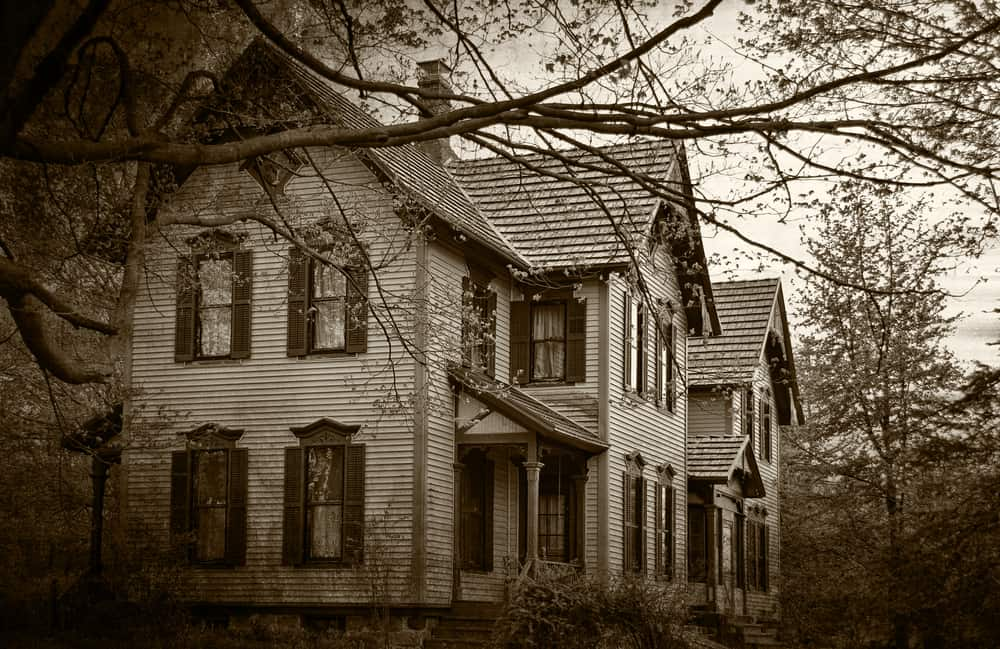haunted places in new england - dark sepia image of old, abandoned looking house with leafless trees