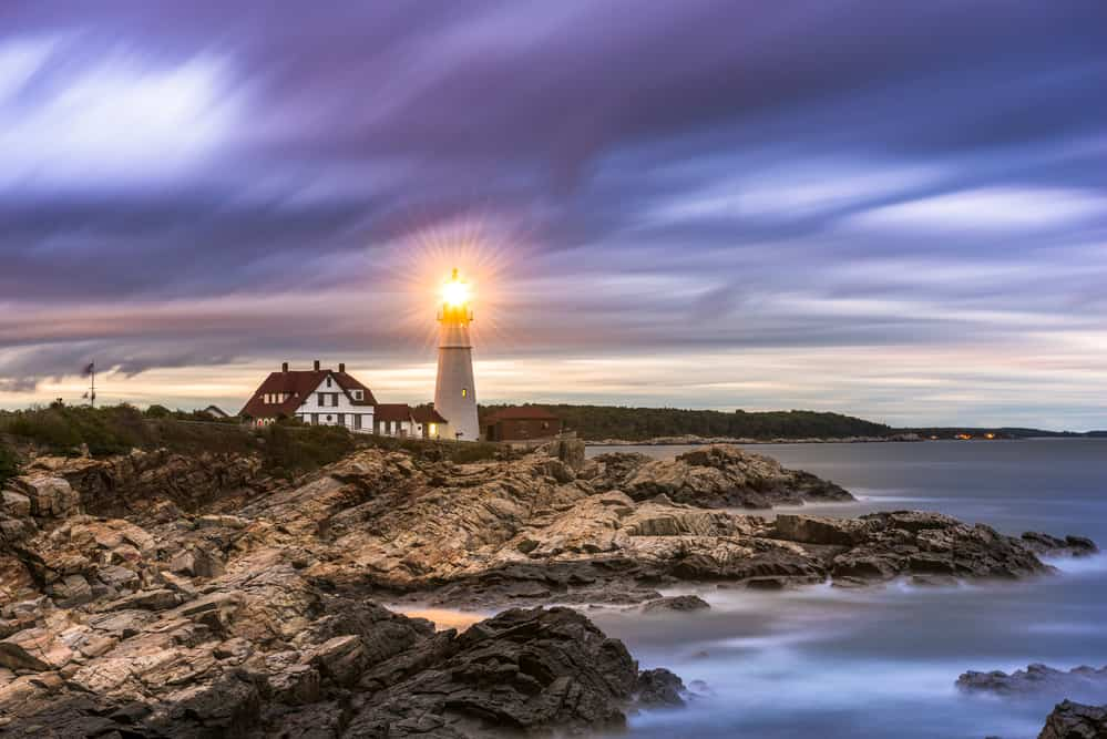 illuminated lighthouse on rocky maine coast at evening