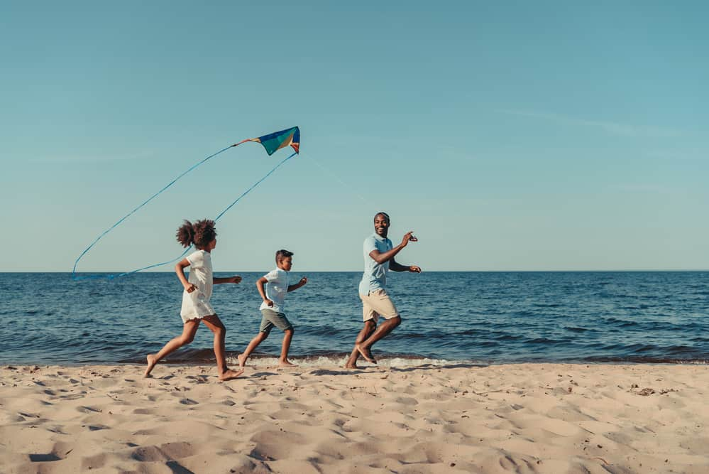 family vacations in new england - father and kites running on a sandy beach at dusk and flying a kite