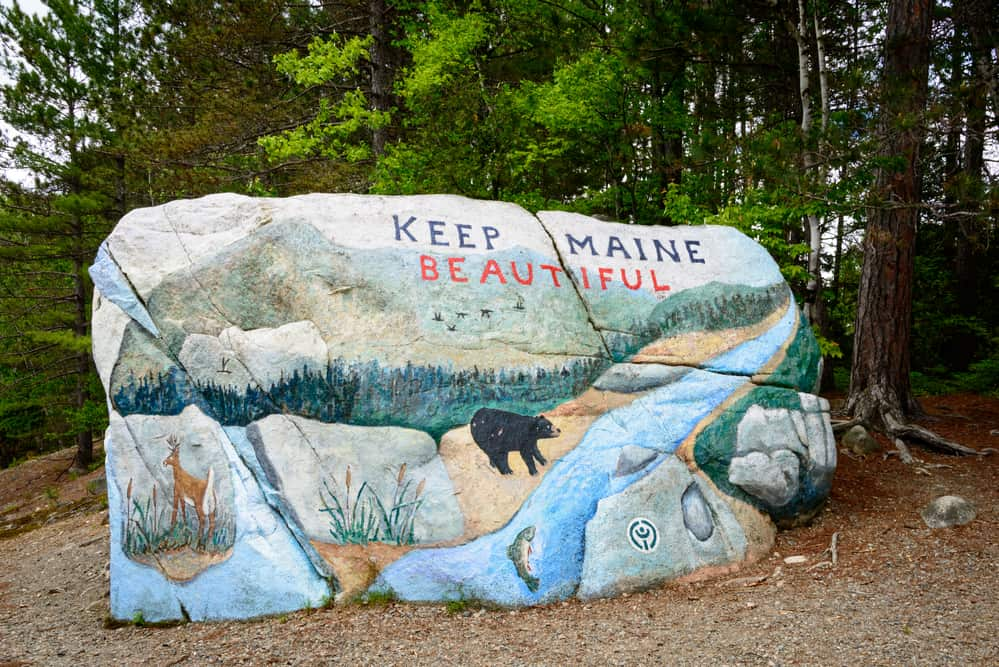 "best hikes in maine - image of a large painted rock in the woods that reads ""keep maine beautiful"""