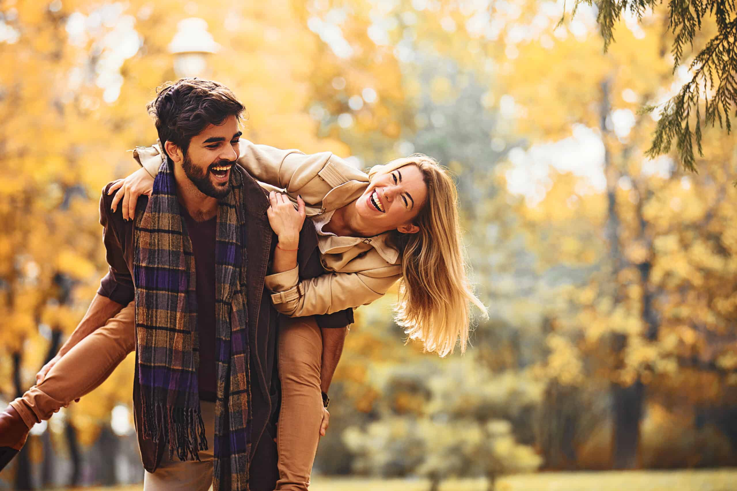 romantic getaways in massachusetts - couple playing piggy back in the park, fall leaves surround them. they both wear scarves