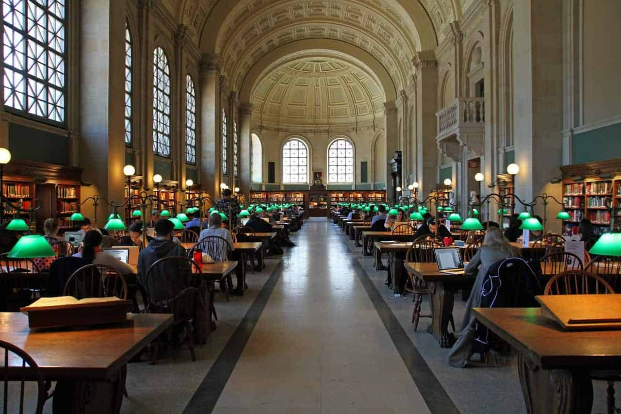 literary sites in boston - image of boston public library interior, grand library with arched roof and dark wooden desks placed on both sides of a long corridor