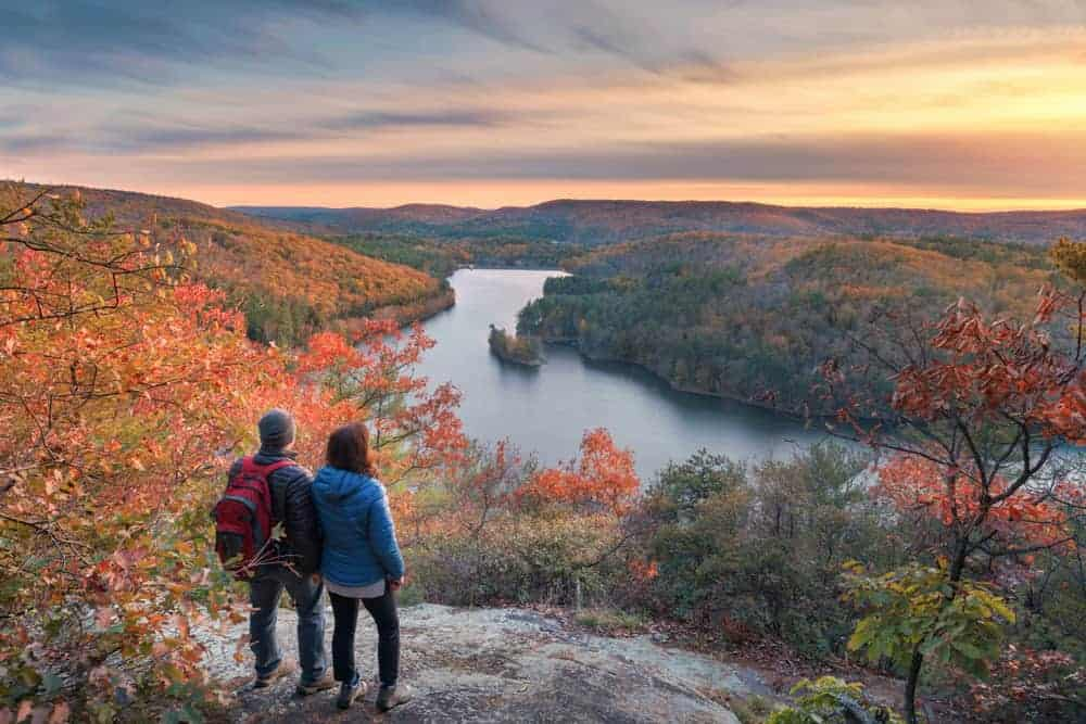 romantic getaways in maine - couple standing atop mountain overlooking river and hills covered in fall foliage