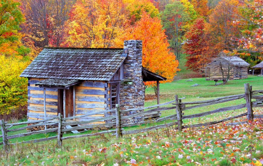 cabins in new hampshire - image of old fashioned log cabin behind wooden fence. colorful fall trees in the background