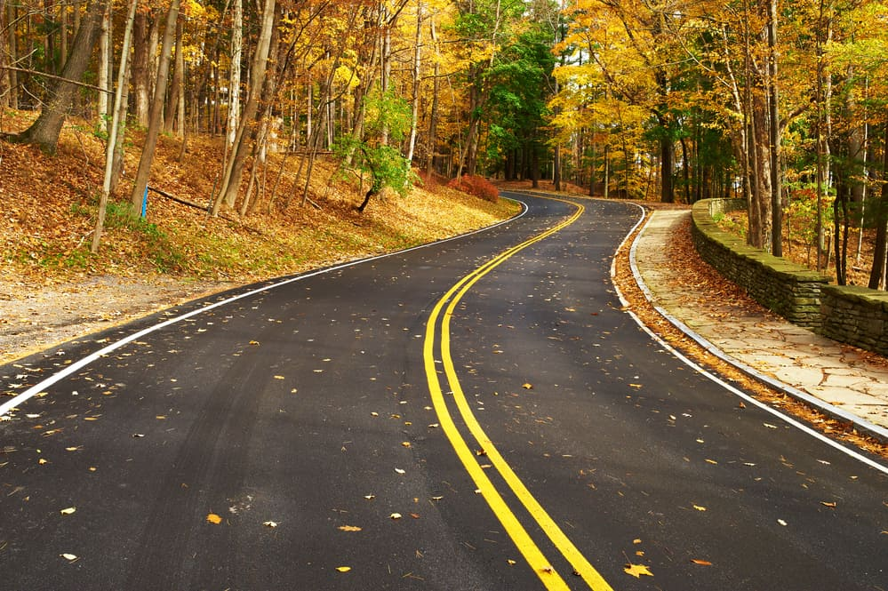 Vermont fall foliage road trips - image of road surrounded by fall trees, no cars on road