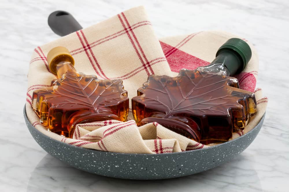 new england gifts - a plate with two maple leaf-shaped bottles of brown maple syrup