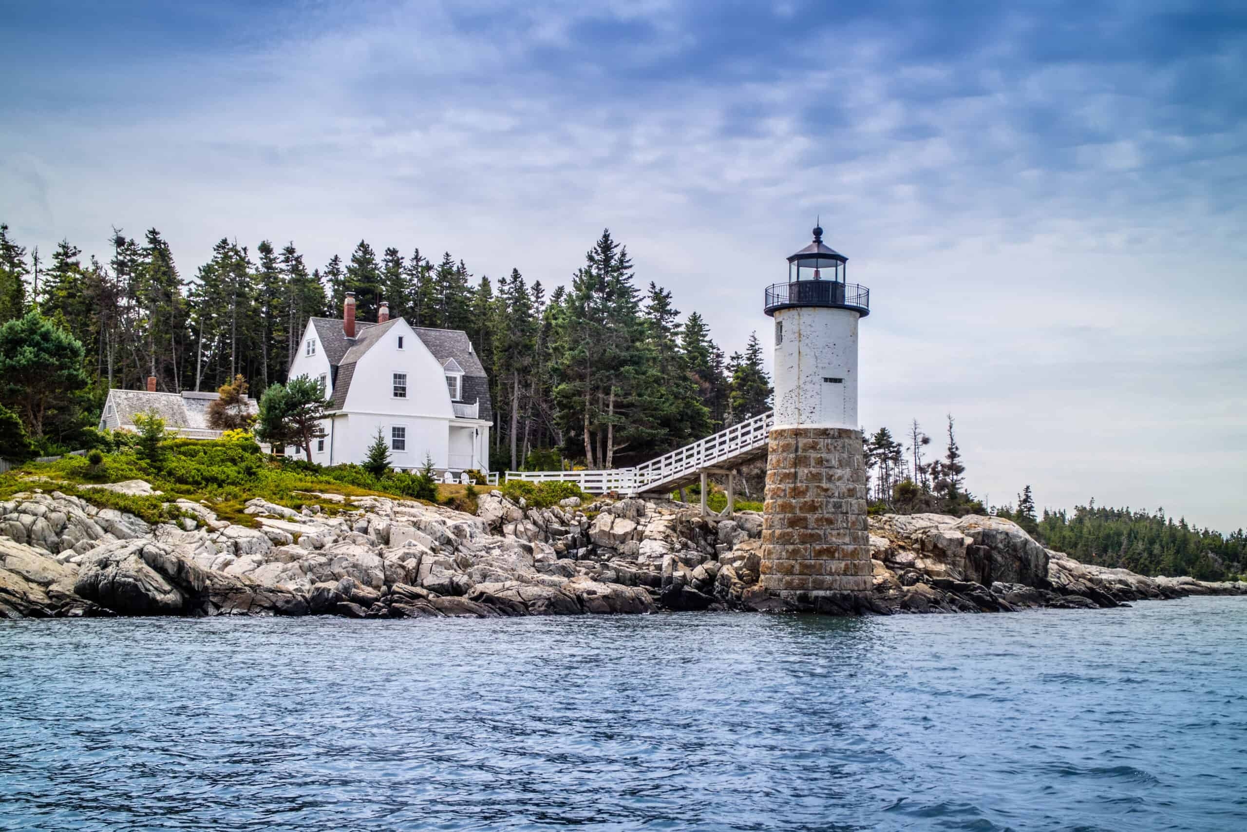 coastal towns in maine - image of a white classic lighthouse with house on a rocky maine coast