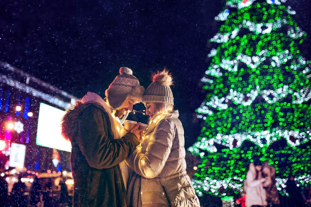 Adult couple hanging out in the city during Christmas time over lights city background and snow at night