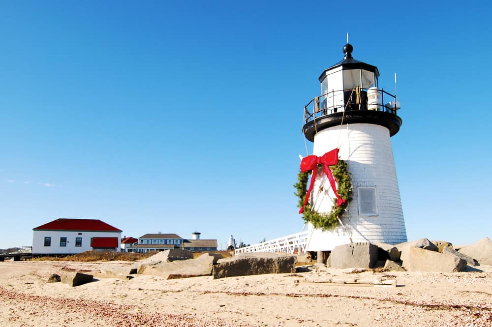 airbnb connecticut - image of white and black lighthouse on a beach with a christmas wreath, blue sky behind