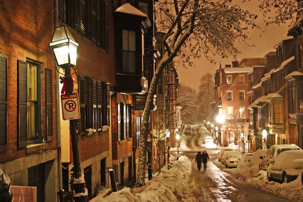 Christmas in Boston - a nighttime image of a snowy Boston street. the street is laden with snow, brick buildings hug the road. the light is hazy