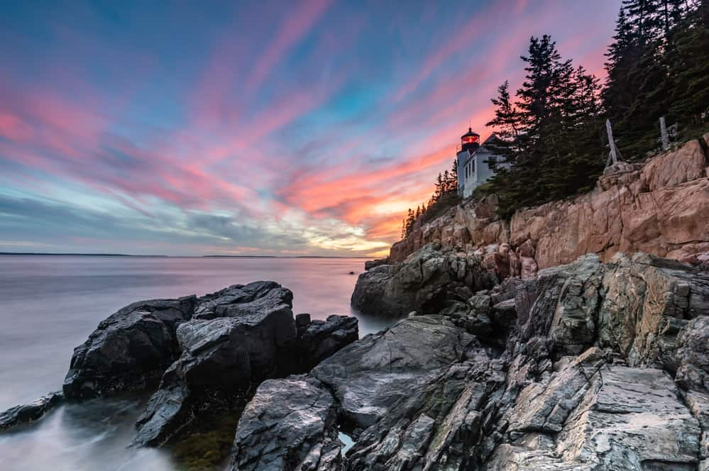 weekend getaways from boston - sunset image of rocky maine coast with lighthouse