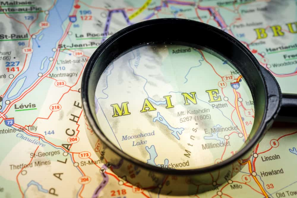 things to do in maine - image of maine on a map, with the name highlighted under a magnifying glass