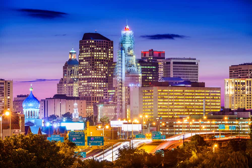 things to do in hartford ct - Hartford, Connecticut, USA downtown city skyline over the highway., purple hued sunset over city skyline