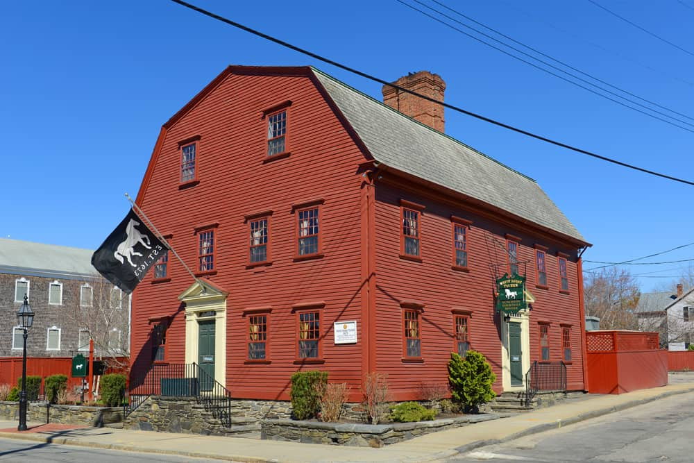 a historic red building in new england, set against a bright blue sky