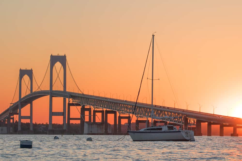 image of an inlet with a long, iconic bridge spanning it. sailboats in foreground. the sun is setting