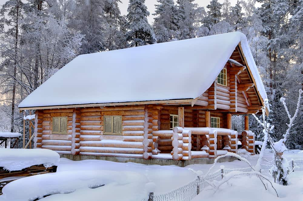 cabins in maine - image of snow covered log cabin in thick wintry forest