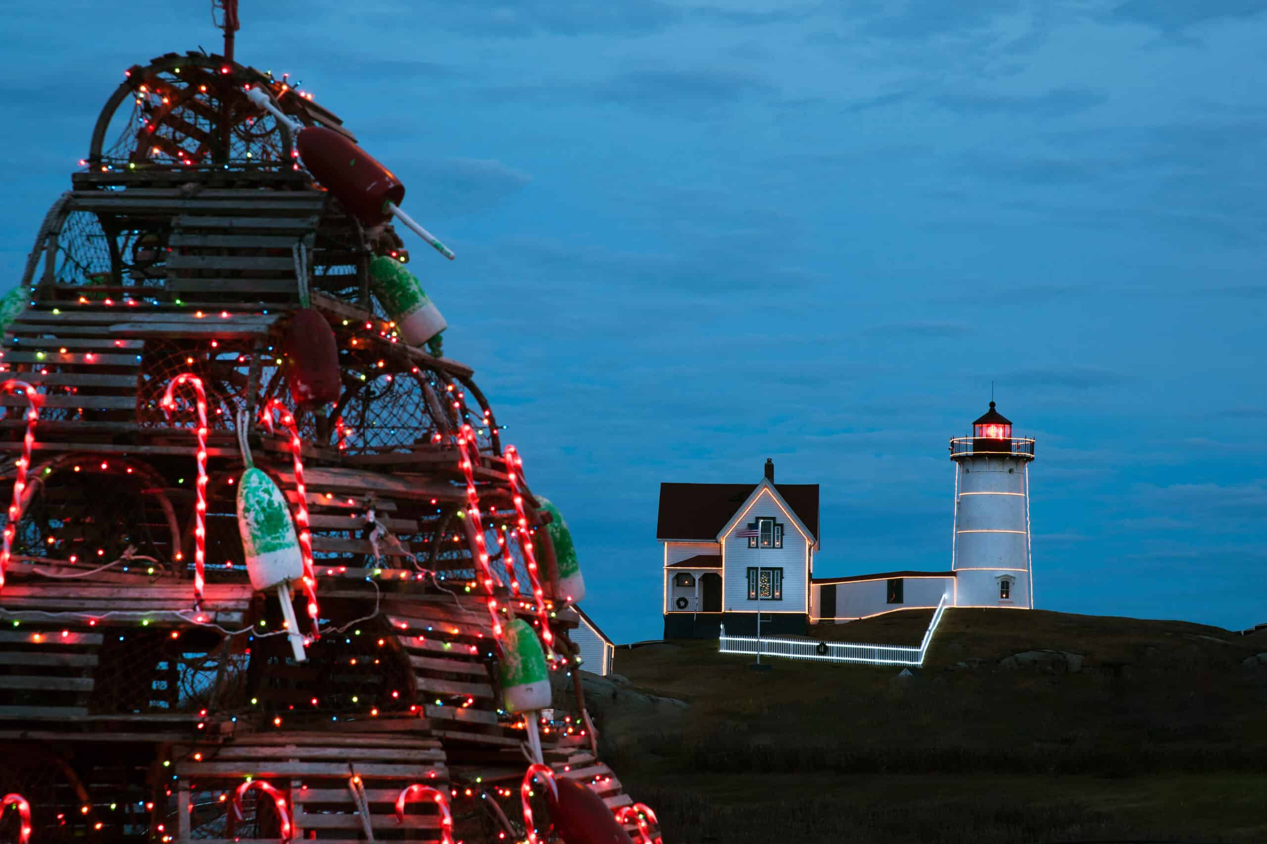christmas in maine - Nubble lighthouse is decorated and lit up for the holidays in Maine with traditional wooden lobster trap holiday tree in the foreground.