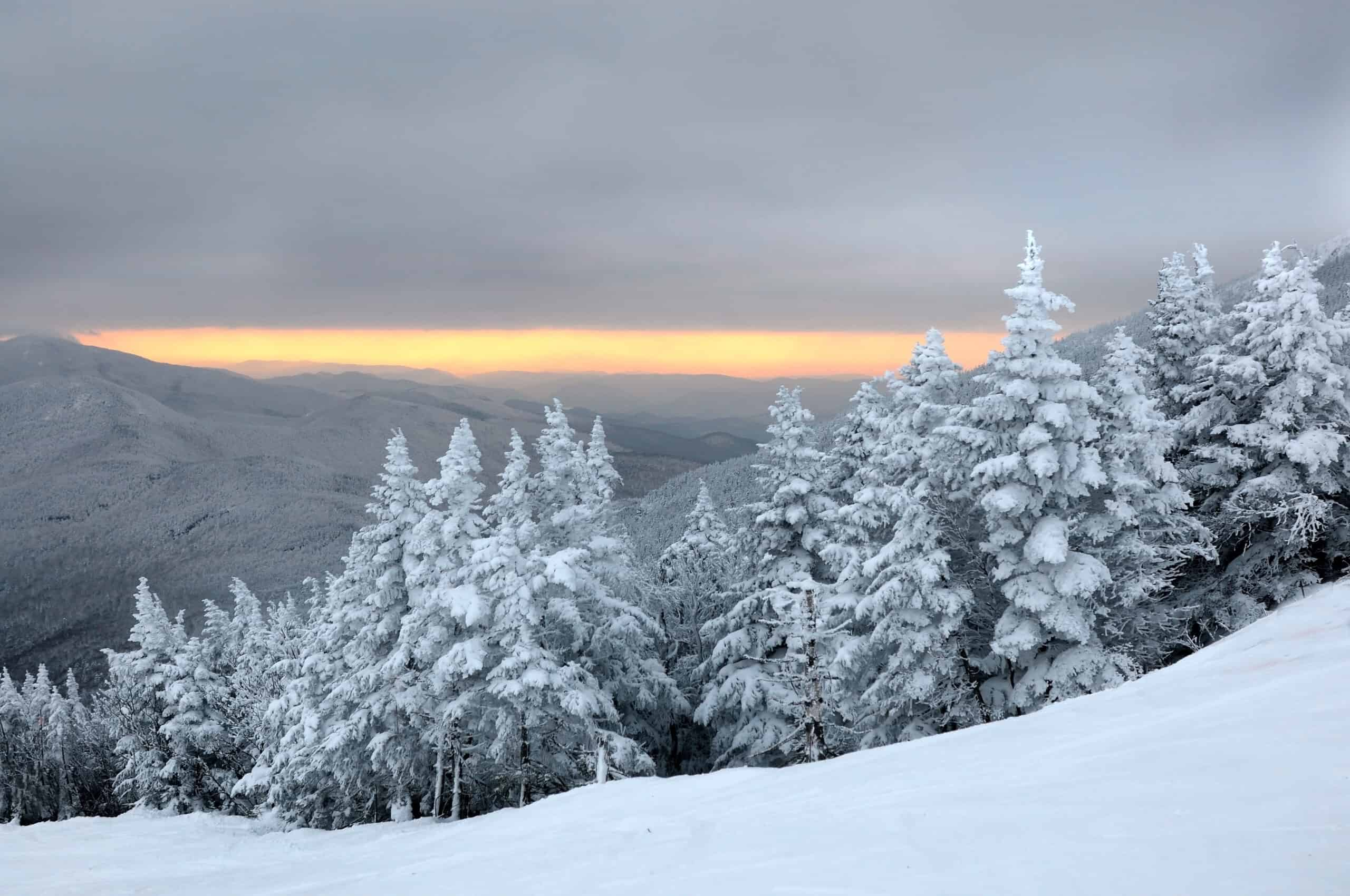 best ski resorts in vermont - image of snow covered trees with cloudy winter sunset in background