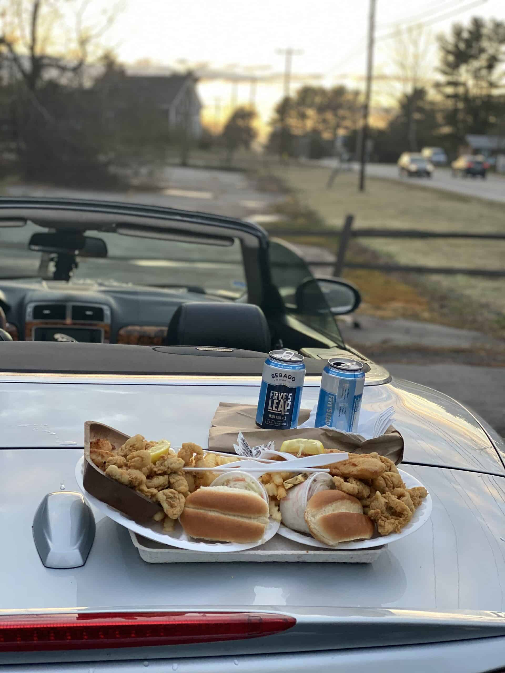 lobster pounds in maine - image of fried seafood and cans of beer on the hood of a convertible, sunset