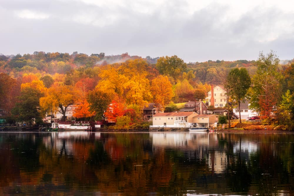 best places to visit in connecticut - image of fall scene in calm Connecticut, houses by lake with foliage in background