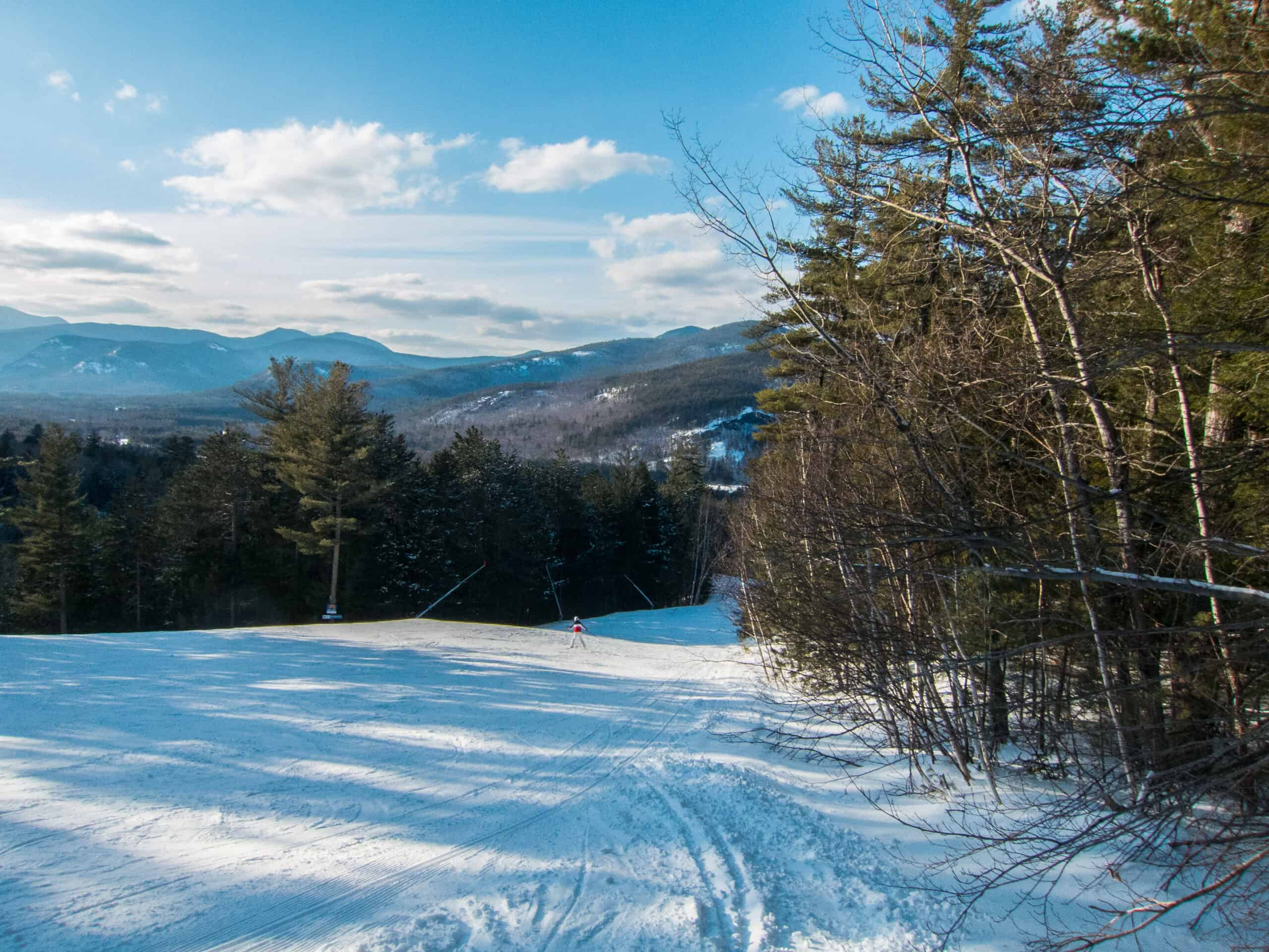 best ski resorts in NH - image of sunny day on a sleek snowy mountain, blue sky in distance