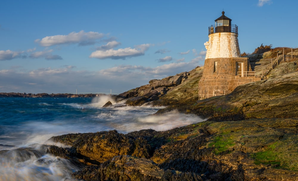 best places to visit in rhode island - image of classic New England lighthouse on coast near Newport, RI sunny day
