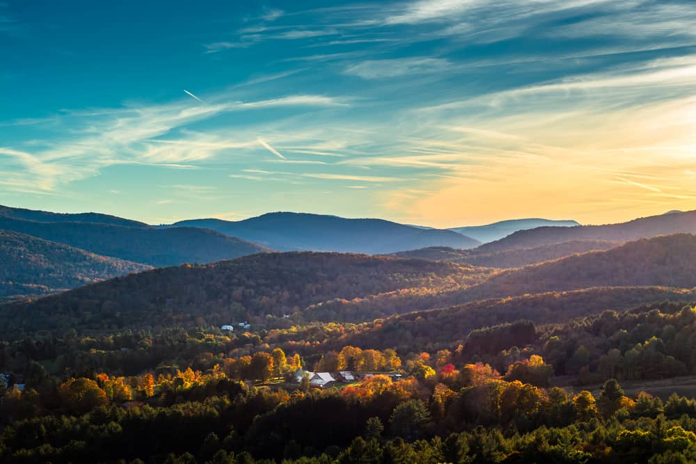 places to visit in vermont - image of distant mountains at dusk with fall foliage visible in the valley