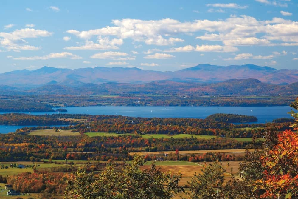 hikes near burlington vt header image - photo of distant mountains and lake with fall foliage dotting the scene