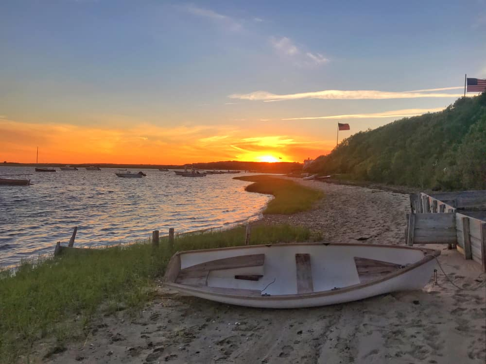best beaches on cape cod - image of sunset over small beach with abandoned row boat, cape cod massachusetts